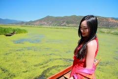 在红色礼服的亚洲中国秀丽有在头的红色scraf的,在云南鹿谷草湖,享受业余时间 库存照片