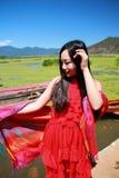在红色礼服的亚洲中国秀丽有在头的红色scraf的,在云南鹿谷草湖,享受业余时间 图库摄影