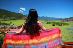 在红色礼服的亚洲中国秀丽有在头的红色scraf的,在云南鹿谷草湖,享受业余时间 免版税库存照片
