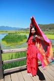 在红色礼服的亚洲中国秀丽有在头的红色scraf的,在云南鹿谷草湖,享受业余时间 免版税库存图片