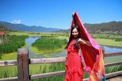 在红色礼服的亚洲中国秀丽有在头的红色scraf的,在云南鹿谷草湖,享受业余时间 免版税图库摄影