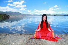 在红色礼服的亚洲中国秀丽有在头的红色scraf的,在凝思坐在Yunnan鹿谷湖海滩,享受业余时间 库存照片