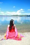 在红色礼服的亚洲中国秀丽有在头的红色scraf的,在凝思坐在Yunnan鹿谷湖海滩,享受业余时间 库存图片