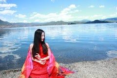 在红色礼服的亚洲中国秀丽有在头的红色scraf的,在凝思坐在Yunnan鹿谷湖海滩,享受业余时间 免版税库存图片