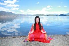在红色礼服的亚洲中国秀丽有在头的红色scraf的,在凝思坐在Yunnan鹿谷湖海滩,享受业余时间 免版税库存照片