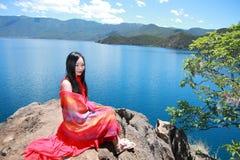 在红色礼服的亚洲中国秀丽有在头的红色scraf的,在石头坐在Yunnan鹿谷湖海滩,享受业余时间 免版税库存图片