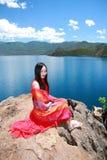 在红色礼服的亚洲中国秀丽有在头的红色scraf的,在石头坐在Yunnan鹿谷湖海滩,享受业余时间 免版税库存照片
