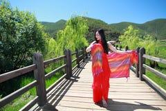 在红色礼服的亚洲中国秀丽有在头的红色scraf的,在走的婚姻桥梁云南鹿谷草湖,享受业余时间 库存图片