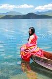 在红色礼服的亚洲中国秀丽有在头的红色scraf的,在Mosuo特别独木舟坐在Yunnan鹿谷湖,享受业余时间 免版税图库摄影