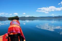 在红色礼服的亚洲中国秀丽有在头的红色scraf的,在Mosuo特别独木舟坐在Yunnan鹿谷湖,享受业余时间 库存图片