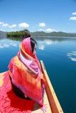 在红色礼服的亚洲中国秀丽有在头的红色scraf的,在Mosuo特别独木舟坐在Yunnan鹿谷湖,享受业余时间 免版税库存照片