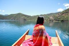 在红色礼服的亚洲中国秀丽有在头的红色scraf的,在Mosuo特别独木舟坐在Yunnan鹿谷湖,享受业余时间 免版税库存图片