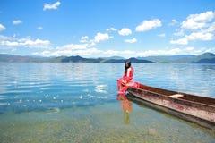 在红色礼服的亚洲中国秀丽有在头的红色scraf的,在Mosuo特别独木舟坐在Yunnan鹿谷湖,享受业余时间 库存照片
