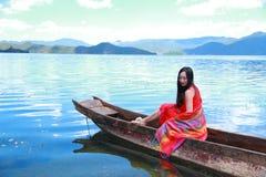 在红色礼服的亚洲中国秀丽有在头的红色scraf的,在Mosuo特别独木舟坐在Yunnan鹿谷湖,享受业余时间 图库摄影