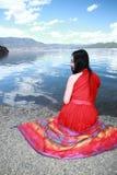 在红色礼服的亚洲中国秀丽有在头的红色scraf的,在Yunnan鹿谷湖海滩,享受业余时间 免版税库存照片