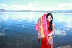 在红色礼服的亚洲中国秀丽有在头的红色scraf的,在Yunnan鹿谷湖海滩,享受业余时间 图库摄影