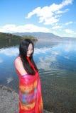 在红色礼服的亚洲中国秀丽有在头的红色scraf的,在Yunnan鹿谷湖海滩,享受业余时间 库存照片