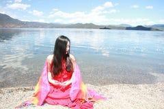 在红色礼服的亚洲中国秀丽有在头的红色scraf的,在Yunnan鹿谷湖海滩,享受业余时间 库存图片