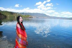 在红色礼服的亚洲中国秀丽有在头的红色scraf的,在Yunnan鹿谷湖海滩,享受业余时间 免版税库存图片