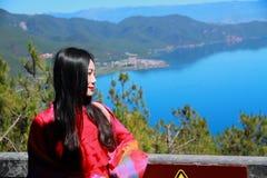 在红色礼服的亚洲中国秀丽有在头的红色scraf的,在Yunnan鹿谷湖,享受业余时间 库存图片