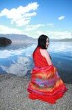 在红色礼服的亚洲中国秀丽有在头的红色scraf的,在Yunnan鹿谷湖,享受业余时间 免版税库存照片