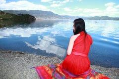 在红色礼服的亚洲中国秀丽有在头的红色scraf的,在Yunnan鹿谷湖,享受业余时间 免版税图库摄影