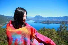 在红色礼服的亚洲中国秀丽有在头的红色scraf的,在Yunnan鹿谷湖,享受业余时间 免版税库存图片