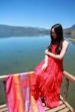 在红色礼服的亚洲中国秀丽有在头的红色scraf的,坐在Yunnan鹿谷湖海滩,享受业余时间 库存照片