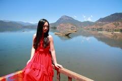 在红色礼服的亚洲中国秀丽有在头的红色scraf的,坐在Yunnan鹿谷湖海滩,享受业余时间 图库摄影