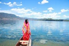 在红色礼服的亚洲中国秀丽有在头,在Mosuo特别独木舟的立场的红色scraf的在Yunnan鹿谷湖,享受业余时间 库存照片