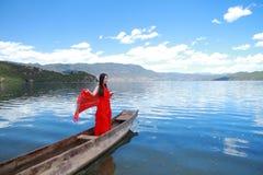 在红色礼服的亚洲中国秀丽有在头,在Mosuo特别独木舟的立场的红色scraf的在Yunnan鹿谷湖,享受业余时间 免版税库存照片