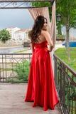 在红色礼服的俏丽的女孩后面用在摆在在一个木地板上的庭院阳台的臀部的手 免版税库存照片