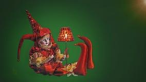 在红色礼服的小丑威尼斯式玩具在绿色背景 库存照片