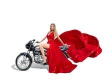 在红色礼服的美丽的年轻wiman在摩托车 免版税库存照片