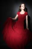 在红色礼服端庄的妇女的时装模特儿 免版税图库摄影
