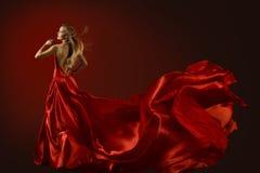 在红色礼服,跳舞的美丽的妇女的时装模特儿舞蹈 免版税库存图片
