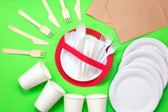 在红色禁止的标志的没有用途标志与在绿色背景的塑料盘 污染概念有害的环境人力的需要回收根土壤结构树 免版税库存照片