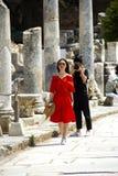 在红色穿戴的旅游妇女走与给人射击她的摄影和游人的姿势 库存照片
