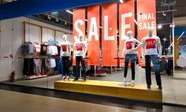 在红色站立在妇女的便衣商店商店窗口显示的海报和时装模特的文本销售在购物中心-销售, 免版税图库摄影
