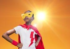 在红色站立用在臀部的手的海角和黄色面具的超级孩子反对明亮的阳光 免版税库存图片
