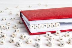 在红色笔记本的木块写的词答复在白色w 库存图片
