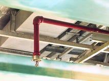 在红色管道系统的自动火喷水隆头 免版税图库摄影