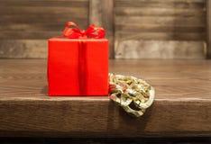 在红色箱子和p金属小珠的礼物从桌边缘垂悬 免版税库存图片