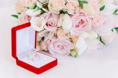 在红色箱子的两只金戒指在白色背景的美丽的creame玫瑰附近 免版税图库摄影