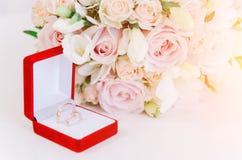 在红色箱子的两只金戒指在白色背景的美丽的creame玫瑰附近 免版税库存图片