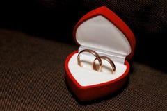 在红色箱子的婚戒在黑暗的背景 免版税图库摄影