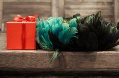 在红色箱子的礼物有从桌边缘的绿松石,蓝色,绿色和黑羽毛的  库存照片