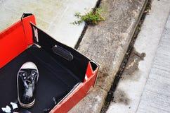 在红色箱子的运动鞋在马路边 库存图片