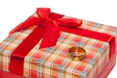 在红色箱子的金戒指与弓的一件礼物的 免版税库存图片