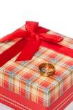 在红色箱子的金戒指与弓的一件礼物的 免版税库存照片